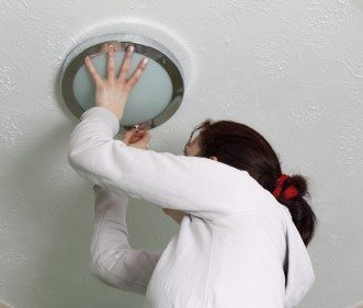 woman replacing light fixture