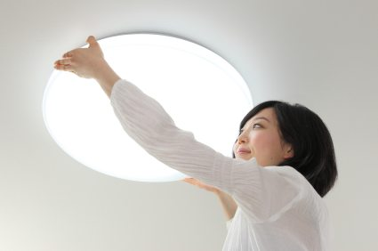 woman installing light fixture